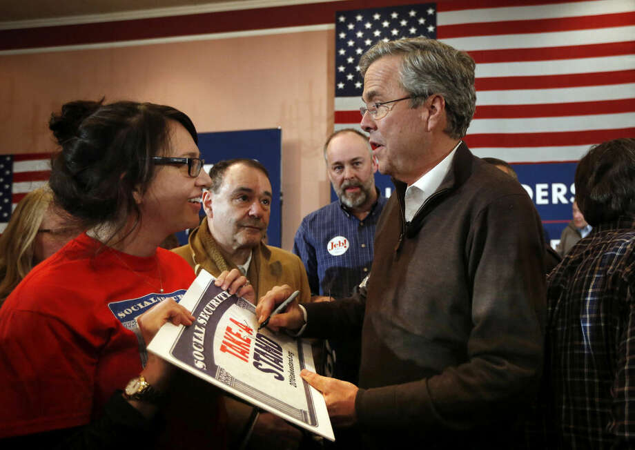 Republican presidential candidate, former Florida Gov. Jeb Bush, autographs a sign for a supporter at a campaign event, Monday, Feb. 8, 2016, in Portsmouth, N.H. (AP Photo/Robert F. Bukaty)