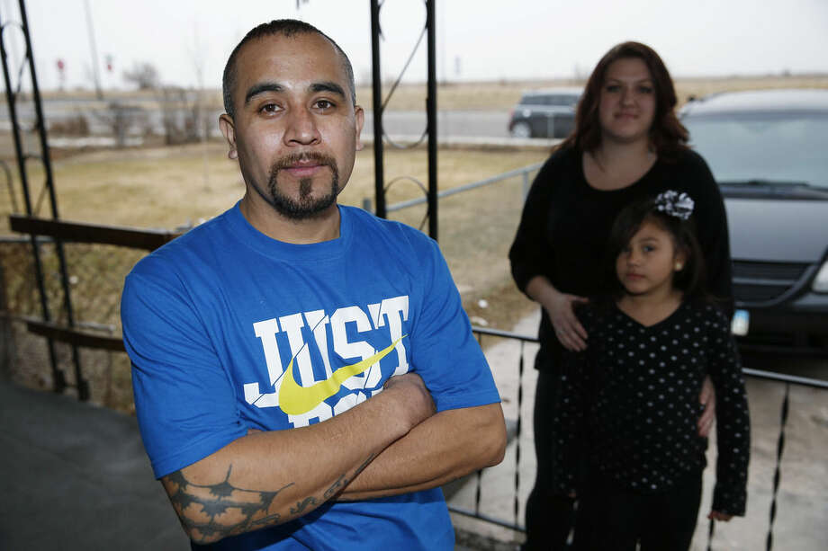 Maximiano Vazquez-Guevara, left, his wife Ashley Bowen, and their 6-year-old daughter, Nevaeh Vazquez, pose for a photo outside their home Saturday, Jan. 31, 2015, in the northeast Denver suburb of Commerce City, Colo. The presidential executive order that fast-tracked immigration hearings for last summer's flood of Central American migrants may have had unintended consequences in canceling hearings for non-detained immigrants with longstanding cases such as Vazquez-Guevara. Vazquez-Guevarra, 34, recently won his appeal to become a legal permanent resident. But his case still needs to go in front of an immigration judge one last time, and it has been pulled from the docket. Thousands of immigrants seeking legalization through the U.S. court system have had their hearings canceled and are being told by the government that it may be 2019 or later before their futures are resolved. (AP Photo/David Zalubowski)
