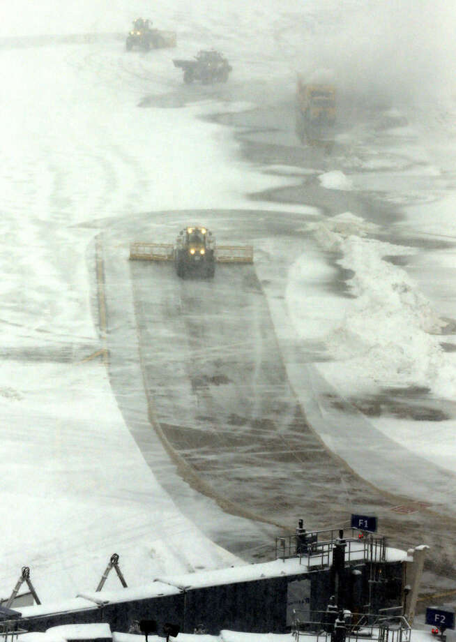 Crews clean snow at O'Hare International Airport on Sunday, Feb. 1, 2015, in Chicago. The first major winter storm of the year is bearing down on the Chicago region, bringing with it blizzard conditions of heavy snow and strong winds. More than 1,100 flights have been canceled at Chicago's airports and snow-covered roads are making travel treacherous. (AP Photo/Nam Y. Huh)