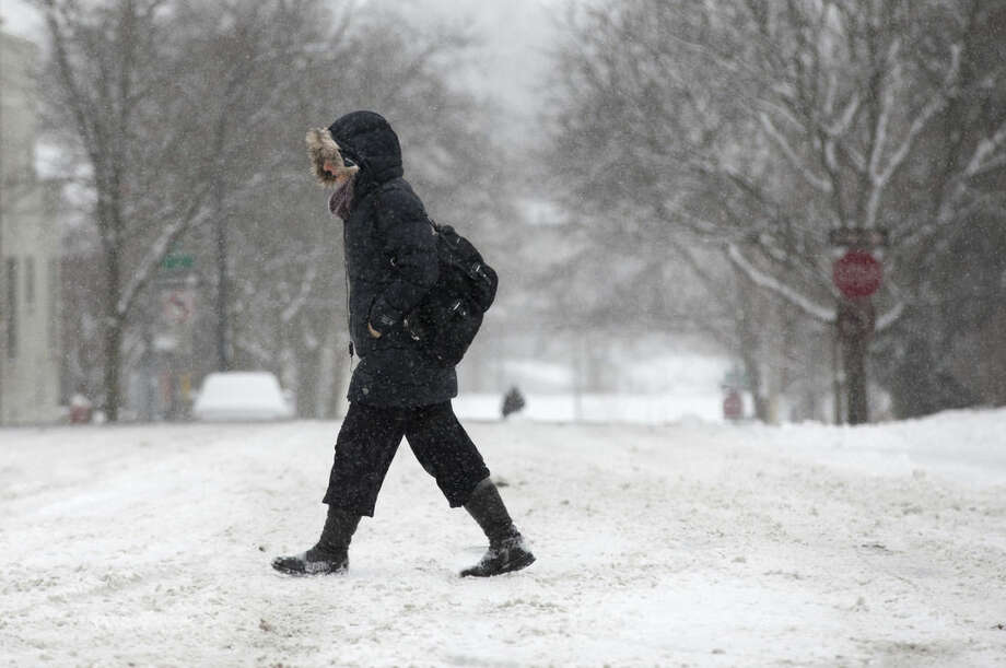 A pedestrian makes their way along Main Street in downtown Ann Arbor, Mich, as more than 2 inches of snow falls on Sunday, Feb. 1, 2015. (AP Photo/The Ann Arbor News, Patrick Record) LOCAL TELEVISION OUT; LOCAL INTERNET OUT