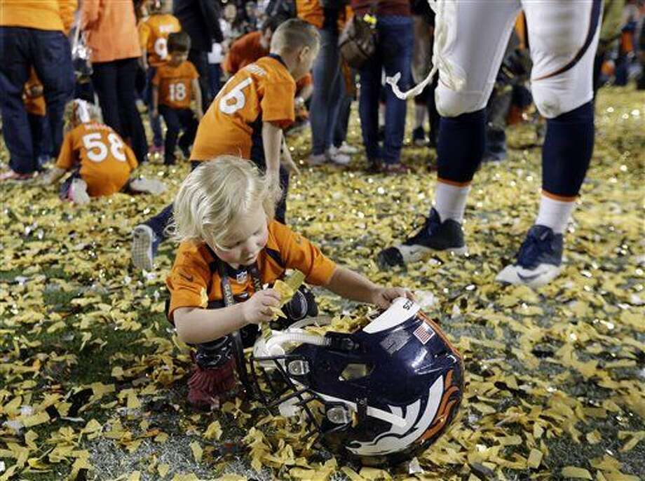 Denver Broncos' Tyler Polumbus daughter Lydia plays with the confetti after the NFL Super Bowl 50 football game Sunday, Feb. 7, 2016, in Santa Clara, Calif. The Broncos won 24-10. (AP Photo/Julie Jacobson)