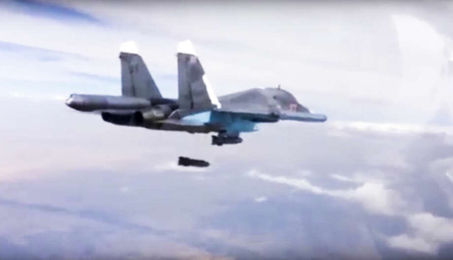 FILE - In this Dec. 9, 2015 file photo made from video footage provided by the Russian Defense Ministry, a Russian Su-34 bomber drops bombs on a target. A new report by a human rights watchdog group accuses Russia of using cluster munitions and unguided bombs on civilian areas in Syria in attacks that it says have killed hundreds of people. The report by Amnesty International released Wednesday, Dec. 23, 2015, says there has been a surge in reports of the use of cluster munitions in the areas being targeted by Russian forces since Moscow formally joined the conflict Sept. 30. (Russian Defense Ministry Press Service via AP, File)