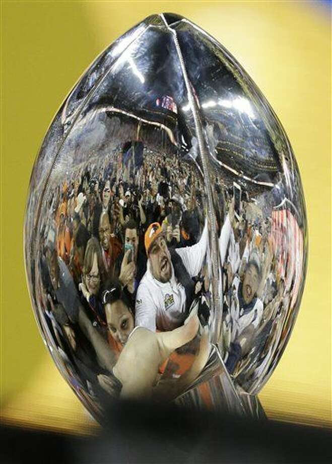 Denver Broncos fans and players were reflected on the trophy as they celebrate after the NFL Super Bowl 50 football game Sunday, Feb. 7, 2016, in Santa Clara, Calif. The Broncos beat the Panthers 24-10. (AP Photo/Gregory Bull)