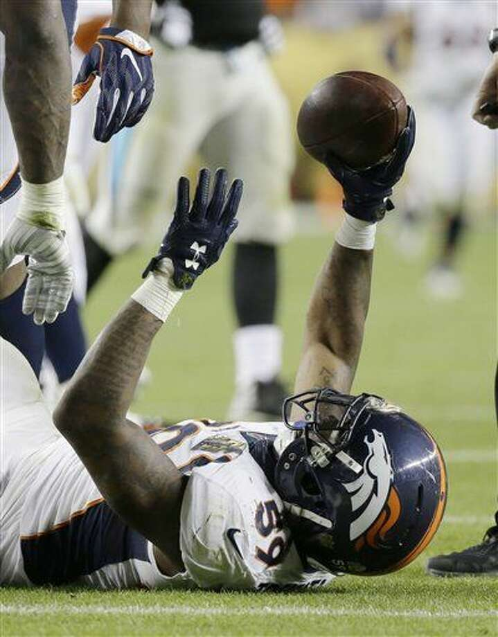 Denver Broncos' Danny Trevathan (59) holds the ball after recovering a fumble by Broncos' T.J. Ward (43), who had intercepted a pass by Panthers' quarterback Cam Newton, during the second half of the NFL Super Bowl 50 football game Sunday, Feb. 7, 2016, in Santa Clara, Calif. (AP Photo/Ben Margot)