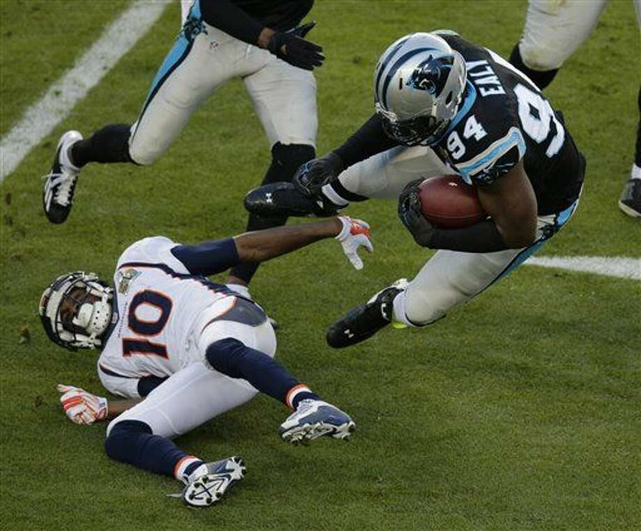 Carolina Panthers' Kony Ealy (94) is tackled by Denver Broncos' Emmanuel Sanders (10) after intercepting a pass during the first half of the NFL Super Bowl 50 football game Sunday, Feb. 7, 2016, in Santa Clara, Calif. (AP Photo/Charlie Riedel)