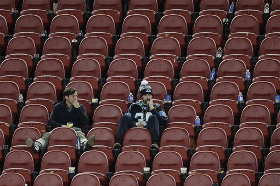 In this Sunday, Feb. 7, 2016, photo, Carolina Panthers fans sit in the stands after the NFL Super Bowl 50 football game where the Broncos won 24-10 in Santa Clara, Calif. According to observers of satellite tracking data, North Korea's newest satellite Kwangmyongsong 4, which launched Sunday, passed almost right over the stadium just an hour after the Super Bowl ended. (AP Photo/Charlie Riedel)