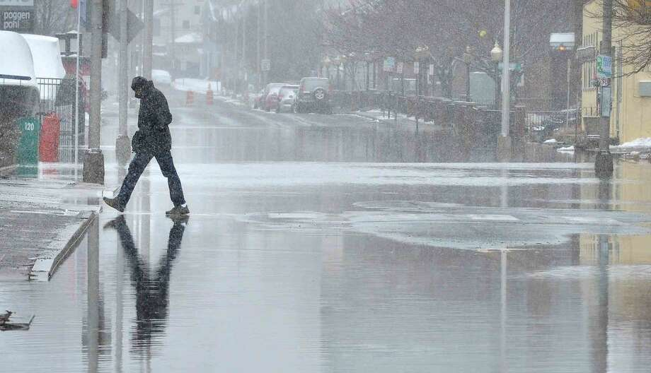 Hour Photo/Alex von Kleydorff A pedestrain makes his way across Water St. after finding a high spot on the flooded road