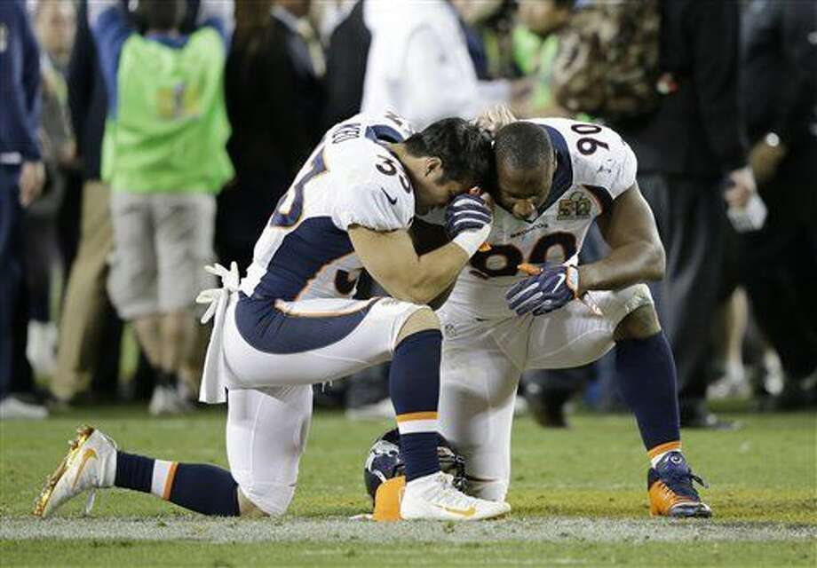 Denver Broncos' Shiloh Keo (33) and Antonio Smith (90) kneel in prayer after the NFL Super Bowl 50 football game against the Carolina Panthers, Sunday, Feb. 7, 2016, in Santa Clara, Calif. The Broncos won 24-10. (AP Photo/Ben Margot)