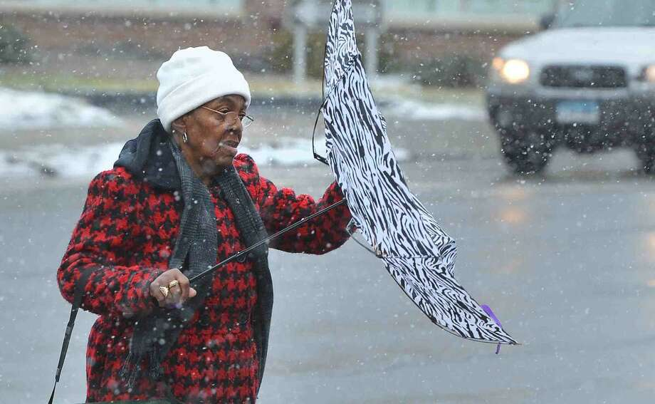 Hour Photo/Alex von Kleydorff Snowy and windy conditions in Norwalk on Monday Morning caused this pedestrian to hold on to her umbrella on Belden Ave.
