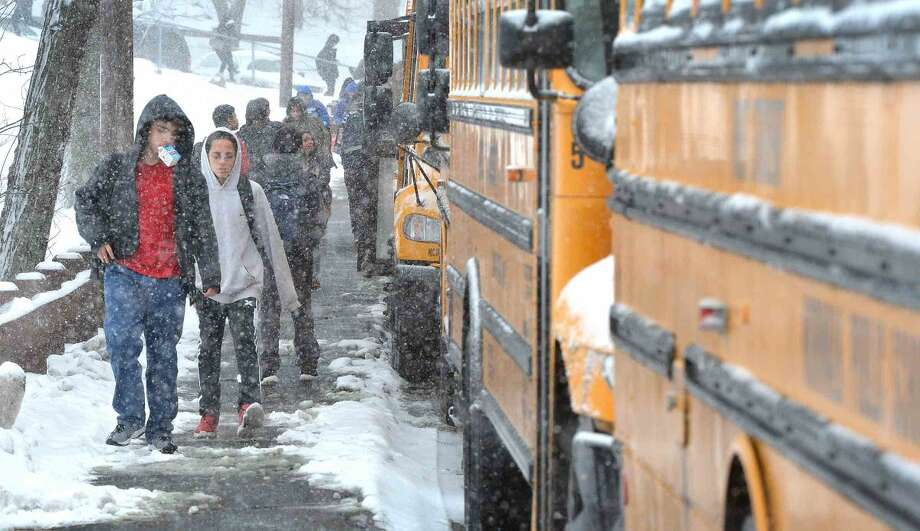 Hour Photo/Alex von Kleydorff Norwalk High School students head for the busses for a two hour early dismissal for all Norwalk Public schools on Monday due to winter weather