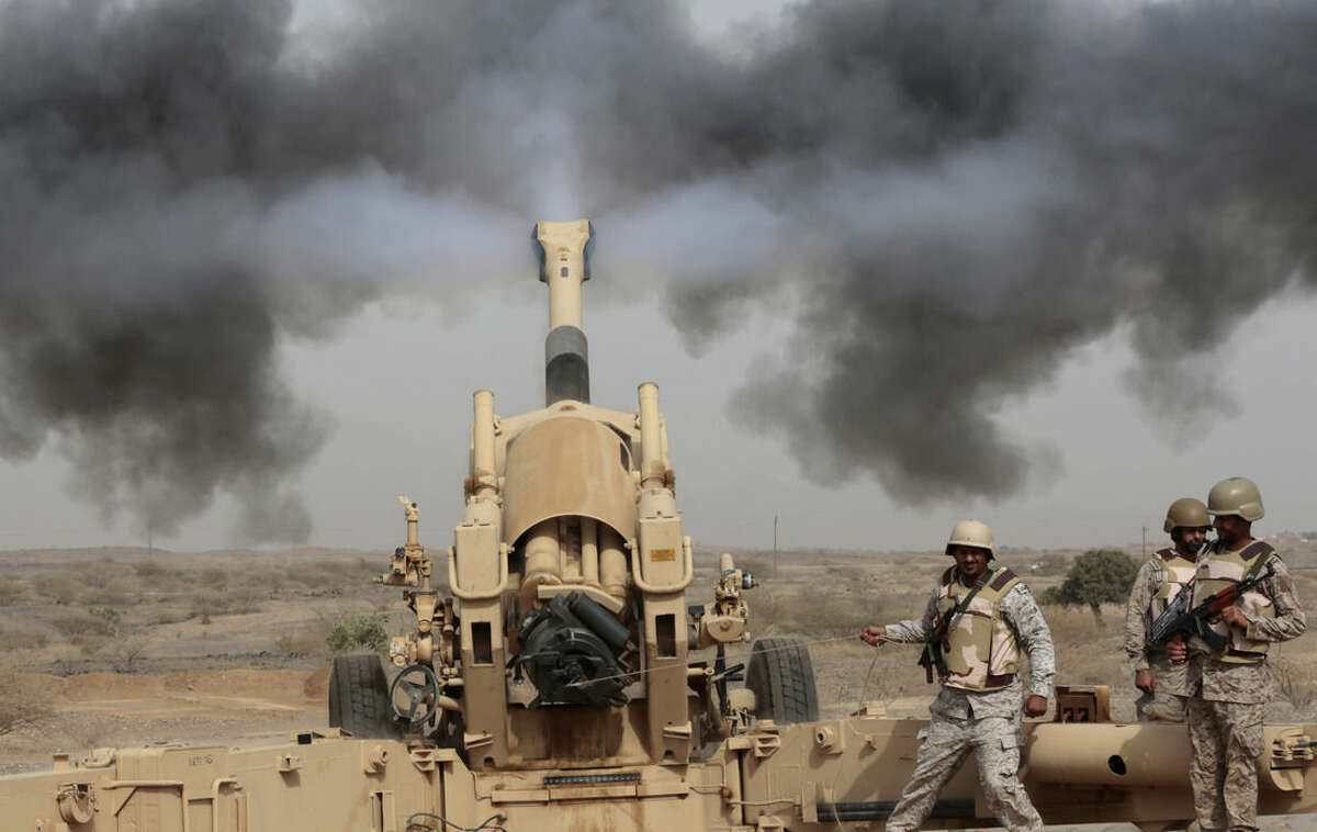 FILE - In this April 20, 2015 file photo, Saudi soldiers fire artillery toward three armed vehicles approaching the Saudi border with Yemen in Jazan, Saudi Arabia. Saudi Arabia's offer to put boots on the ground to fight Islamic State in Syria is as much about the kingdom's growing determination to flex its military might as it is about answering U.S. calls for more help from Mideast allies. (AP Photo/Hasan Jamali, File)