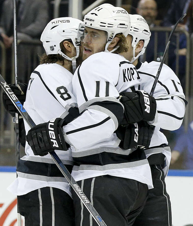 Los Angeles Kings center Anze Kopitar (11) celebrates with defenseman Drew Doughty (8) and left wing Milan Lucic (17) after scoring a goal against the New York Rangers during the first period of an NHL hockey game Friday, Feb. 12, 2016, in New York. (AP Photo/Julie Jacobson)
