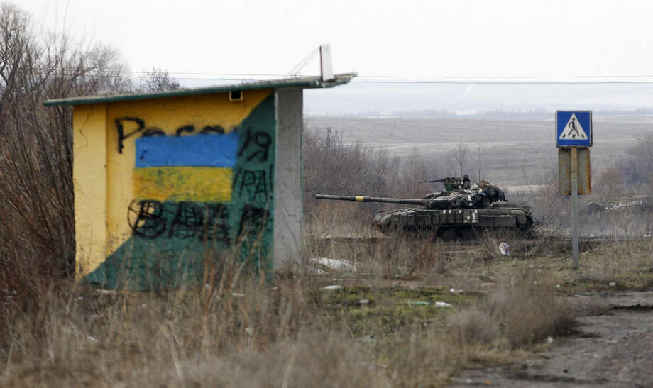A Ukrainian army vehicle drives through fields near the town of Debaltseve, Ukraine, Monday, Feb. 2, 2015. As fighting intensifies between government and rebel forces for control over a key railway hub in the eastern Ukraine town of Debaltseve, separatist leader Alexander Zakharchenko said Monday that he plans to mobilize enough new volunteers to bring his forces to 100,000 men. (AP Photo/Petr David Josek)
