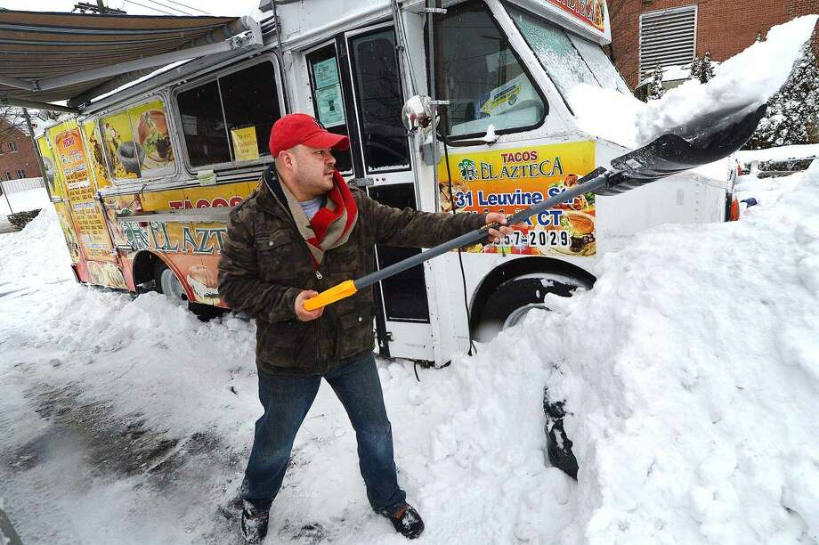 Hour Photo/Alex von Kleydorff Juan Martinez works to clear snow from around his Tacos El Azteca food truck on Main St in Norwalk Monday morning. Martinez rarely closes the truck due to weather and was open today in time for lunch.