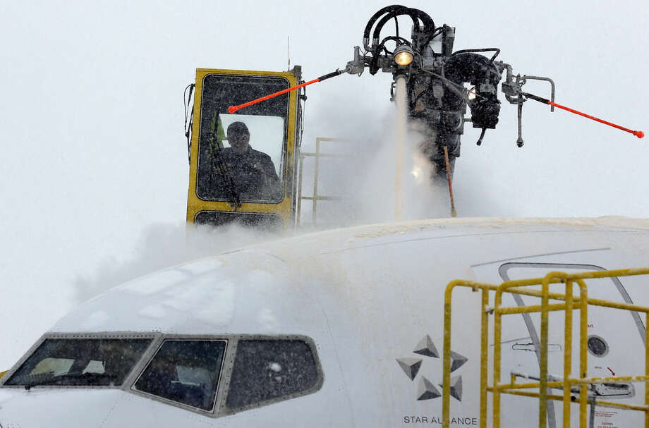 Crews work to de-ice a plane at O'Hare International Airport, Sunday, Feb. 1, 2015, in Chicago. The first major winter storm of the year is bearing down on the Chicago region, bringing with it blizzard conditions of heavy snow and strong winds. More than 1,100 flights have been canceled at Chicago's airports and snow-covered roads are making travel treacherous. (AP Photo/Nam Y. Huh)