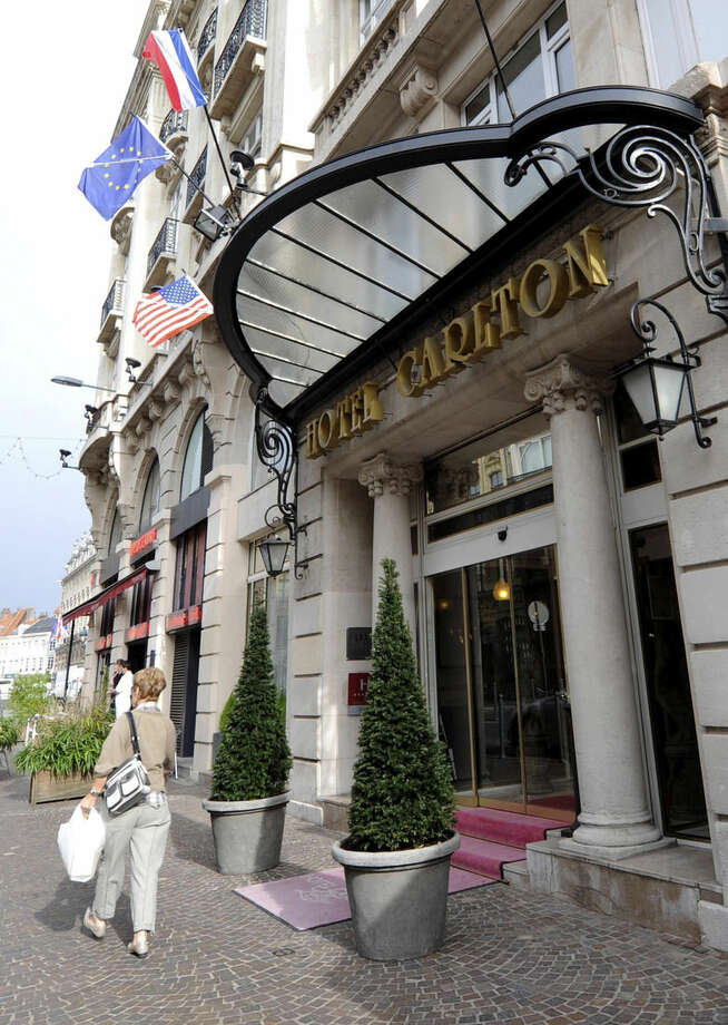 FILE - This Oct. 7, 2011, file photo shows a woman walking past the Carlton hotel in Lille, northern France. Prosecutors in the northern city of Lille are investigating a suspected prostitution ring in France and neighboring Belgium. The head of Lille's luxury Hotel Carlton was among those detained in the probe. A lawyer for Dominique Strauss-Kahn says the former IMF chief wants to be questioned by police so that he can debunk claims that he was linked to a suspected hotel prostitution ring. The French economist known universally by his initials DSK, faces up to 10 years in prison and a 1.5 million euro ($1.7 million) fine on charges of aggravated pimping, along with over a dozen other French and Belgian businessmen and police officers at the trial beginning Monday at a courthouse in the northern French city of Lille. (AP Photo, File)