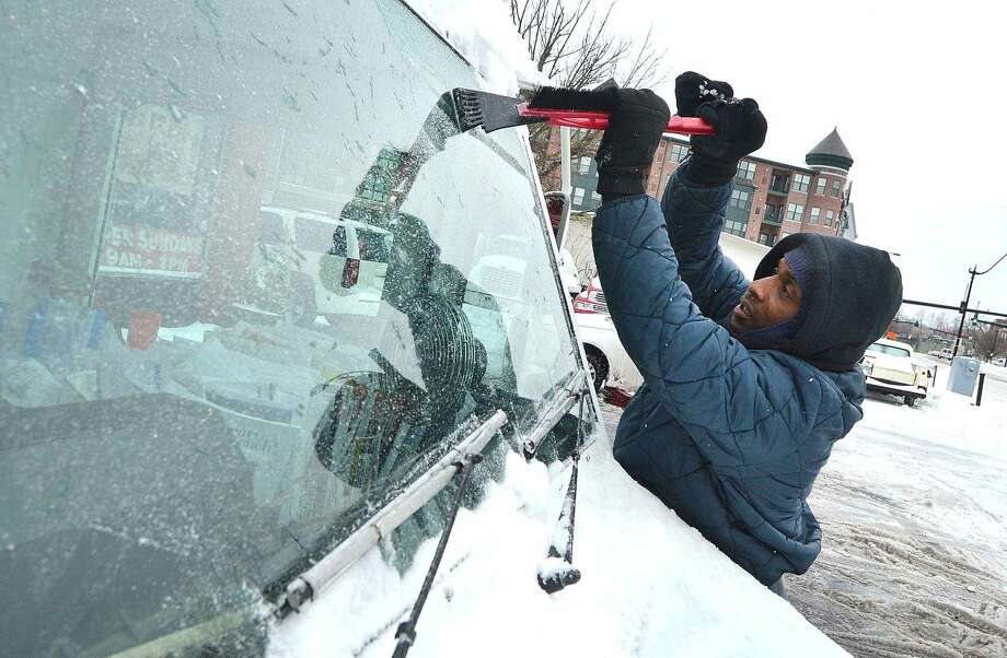 Hour Photo/Alex von Kleydorff Letter Carrier Terrell Johnson scrapes ice from the windshield of his postal vehicle while having chains placed on the tires at Curries Tires Monday morning
