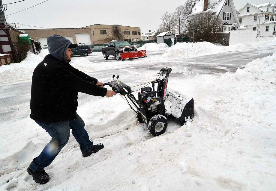 Hour Photo/Alex von Kleydorff Kenneth Murillo Jr. clears snow from the walks around Diamond Deli on Monday. Keeeping pace with the plow truck that pushes snow from the business next door, Kenneth also is the delivery person and will be on the road all day.