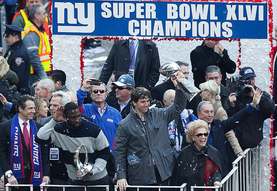 FILE - In this Tuesday, Feb. 7, 2012, file photo, Super Bowl MVP Eli Manning holds aloft the Vince Lombardi Trophy as a float of New York Giants heads up the Canyon of Heroes during a ticker-tape parade, in New York, in celebration of the Giants defeating the New England Patriots in the Super Bowl. Ann Mara, lower right, the matriarch of the NFL's New York Giants for the past 60 years, died Sunday, Feb. 1, 2015. She was 85. (AP Photo/Mark Lennihan, File)