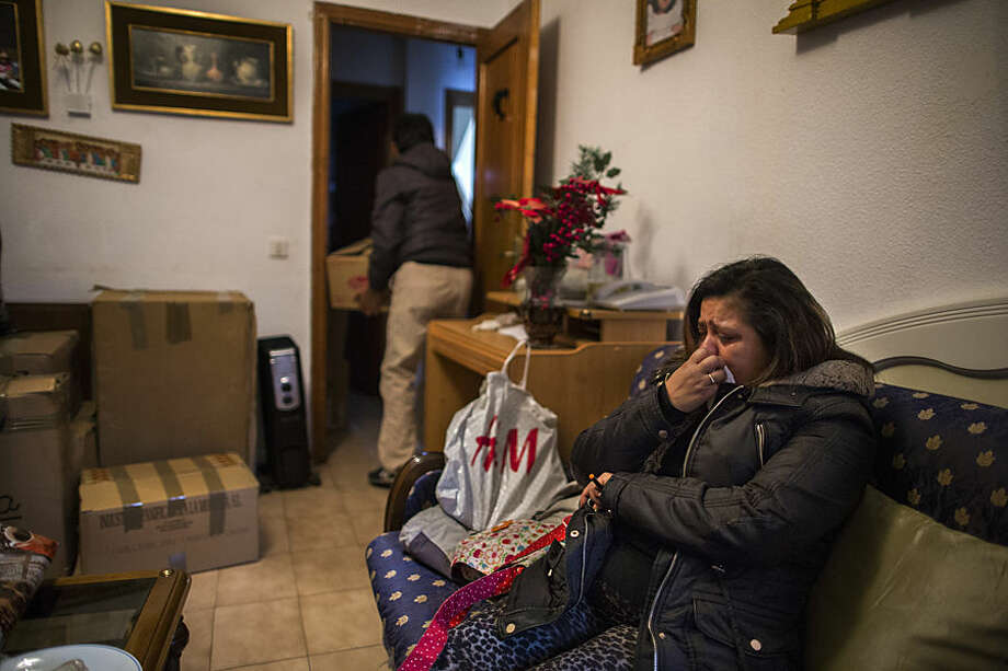 CORRECTS DAY OF THE WEEK TO MONDAY Jessica Bernice Michelena, 40 years old, right, cries as a friend removes her belongings to move out as they expect the police to evict her and her family in Madrid, Spain, Wednesday, Feb. 2, 2015. Jessica and her partner, Eduardo Lucas Zambrano, 37 years old, and their children: Miguel Angel 7 years old, Ana Mile Lucas , 5 years old, occupied an apartment 5 month ago after she lost her job, was evicted from a previous place and lived in the street with her children for 15 days. With her only income of euros 350 ($397) coming from a part time cleaning job she can not afford to pay rent and she barely can buy food. The eviction will take place tomorrow Tuesday, Feb, 3. (AP Photo/Andres Kudacki)