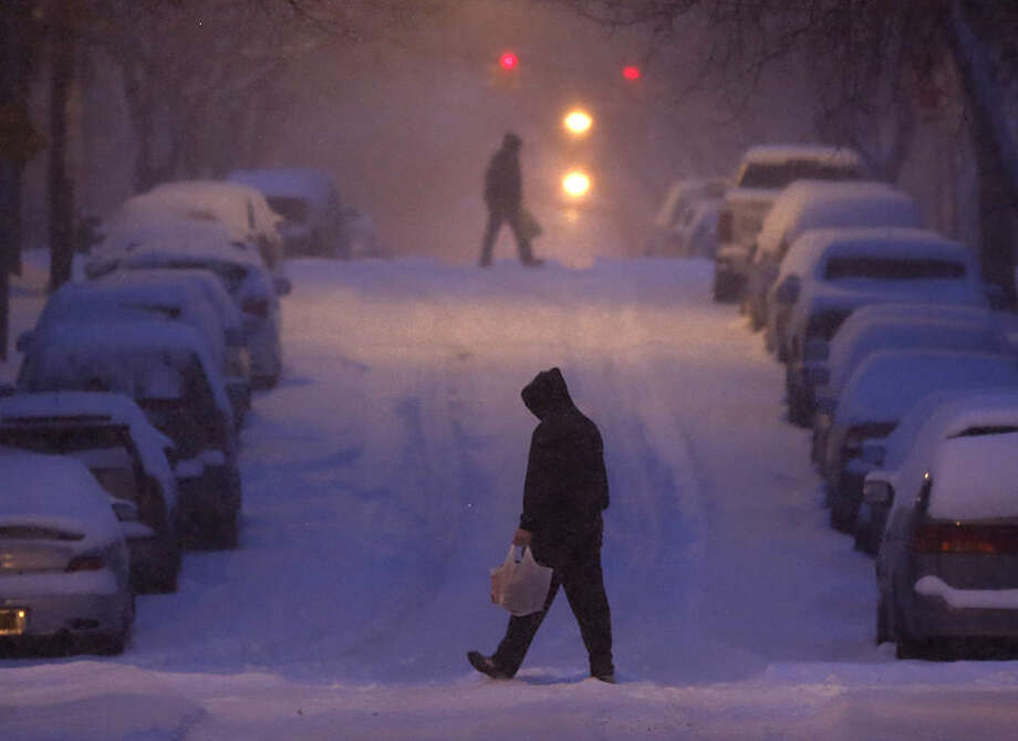 Pedestrians walk in a snowstorm in the Center Square neighborhood, early Monday, Feb. 2, 2015, in Albany, N.Y. (AP Photo/Mike Groll)