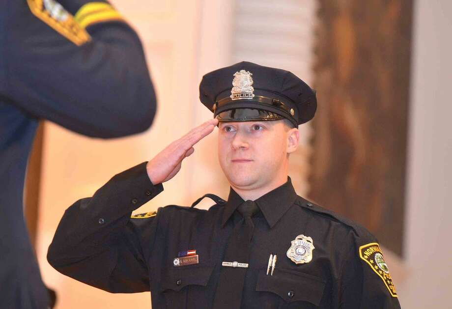 Hour Photo/Alex von Kleydorff Norwalk Police Officer Neil Robertson salutes Chief Kulhawik as he recieves his Meritorious Commendation for his involvement in helping a motorist get his vehicle moved off a railroad crossing when the gates were activated