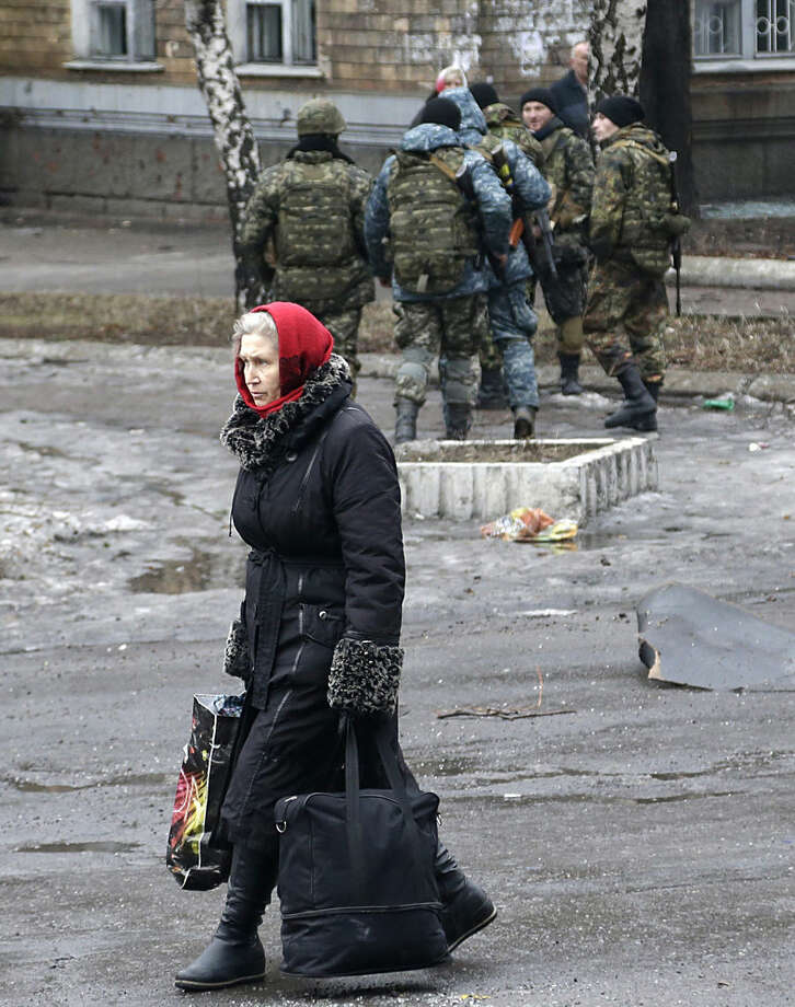 A woman carries her belongings to a building used as an evacuation center in the town of Debaltseve, Ukraine, Tuesday, Feb. 3, 2015. Since the unrest in eastern Ukraine surged anew in early January, the separatists have made notable strides in clawing territory away from the government in Kiev. Their main offensive is now directed at Debaltseve ó a government-held railway junction once populated by 25,000 people that lies between the rebel-held cities of Luhansk and Donetsk. (AP Photo/Petr David Josek)
