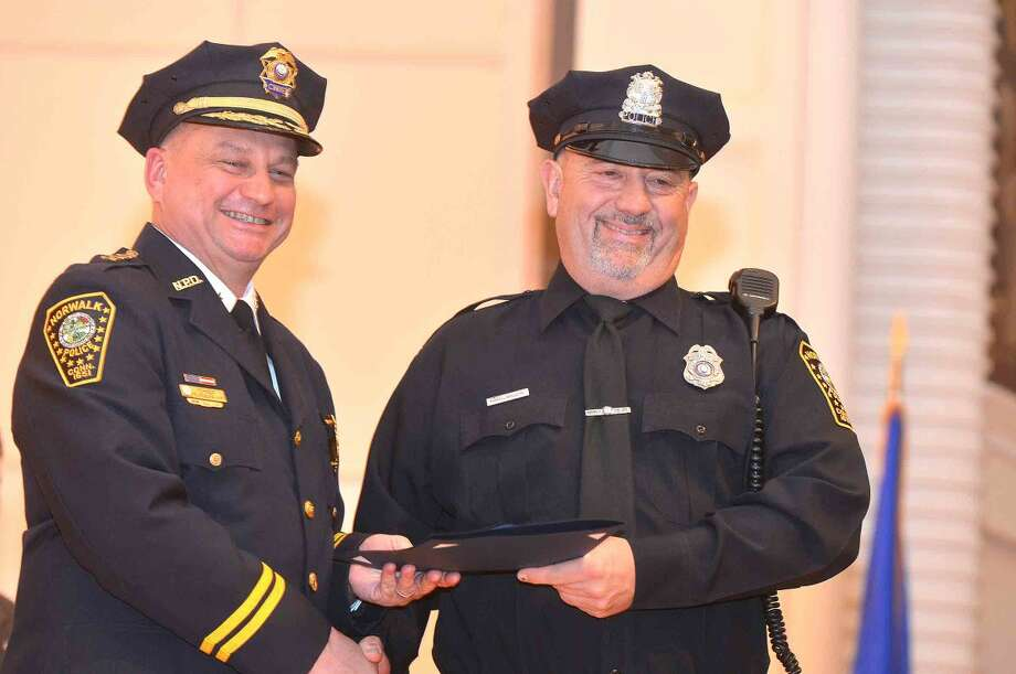 Hour Photo/Alex von Kleydorff Norwalk Police Chief Tom Kulhawik presents Officer Russell Oullette with a Meritorious Commendation for his involvement with other officers in a marine rescue off Shea Island