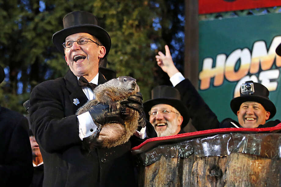 Groundhog Club handler Ron Ploucha, left, holds Punxsutawney Phil, the weather prognosticating groundhog, during the 129th celebration of Groundhog Day on Gobbler's Knob in Punxsutawney, Pa., Monday, Feb. 2, 2015. Phil's handlers said that the groundhog has forecast six more weeks of winter weather. (AP Photo/Gene J. Puskar)