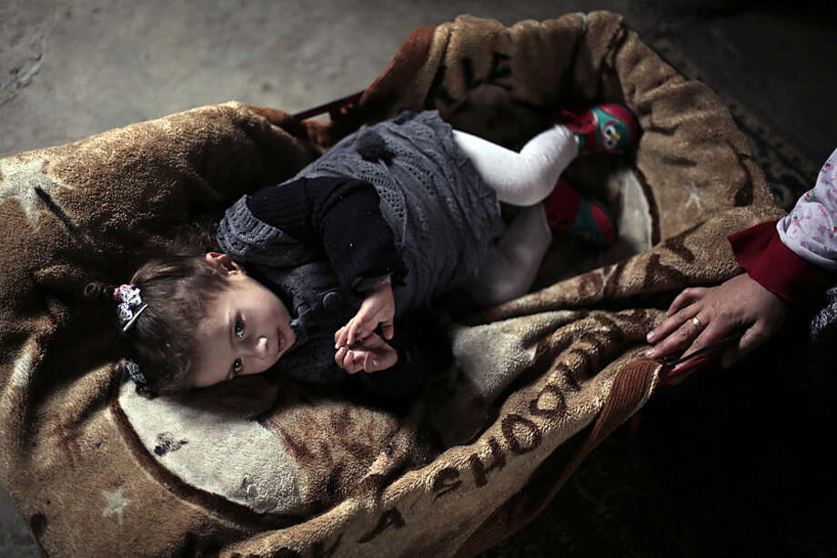 In this Tuesday, Jan. 27, 2015 photo, 36 year-old Palestinian mother Abeer, right, sits near her daughter, 19-month-old Anwar Saad, at their family home in Gaza City. For the Saads, the summer's war in Gaza, the third between Israel and Hamas, came into their home on July 18, 2014 when they say an Israeli tank shell crashed through the wall of their house in Gaza's crowded Shijaiyeh neighborhood. Shrapnel wounded all of the Saad family. Anwar's mother spends much of her time caring for her daughter. The infant only stops crying when she is in her rocking bed. Before the war, Anwar was playful and alert, the mother said. Not any longer. (AP Photo/Khalil Hamra)