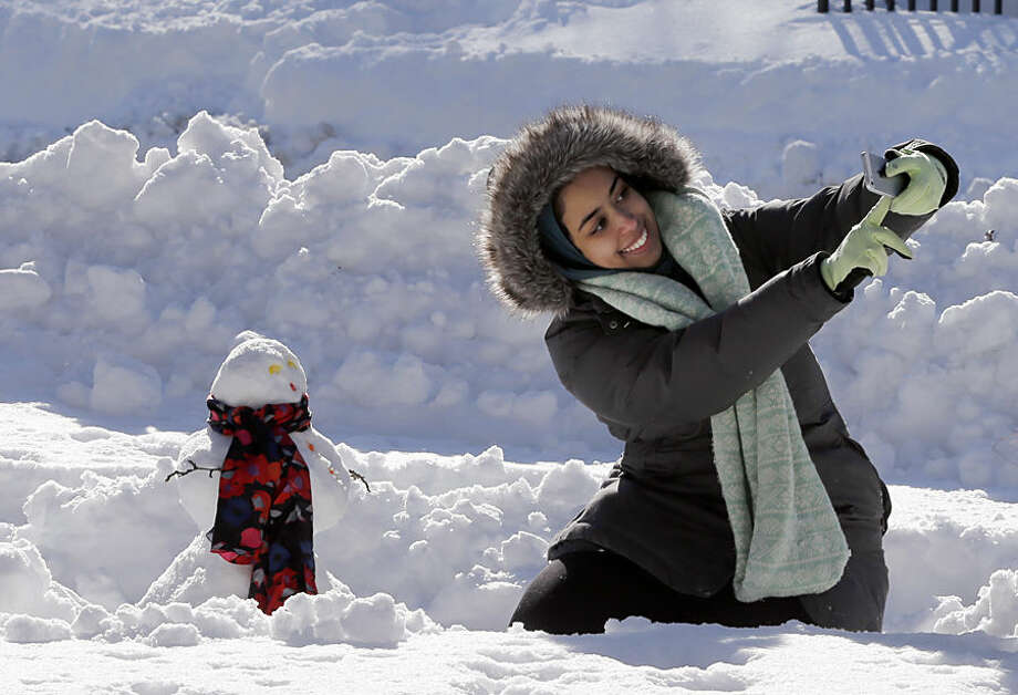 DePaul University student Alaa Hejazi, from Riyadh, Saudi Arabia, shoots a selfie with her very first snowman Monday, Feb. 2, 2015, in Chicago's Millennium Park. The National Weather Service said that the 19.3 inches of snow in Chicago was the fifth highest snowfall total since records started being kept in the late 1800s. (AP Photo/Charles Rex Arbogast)