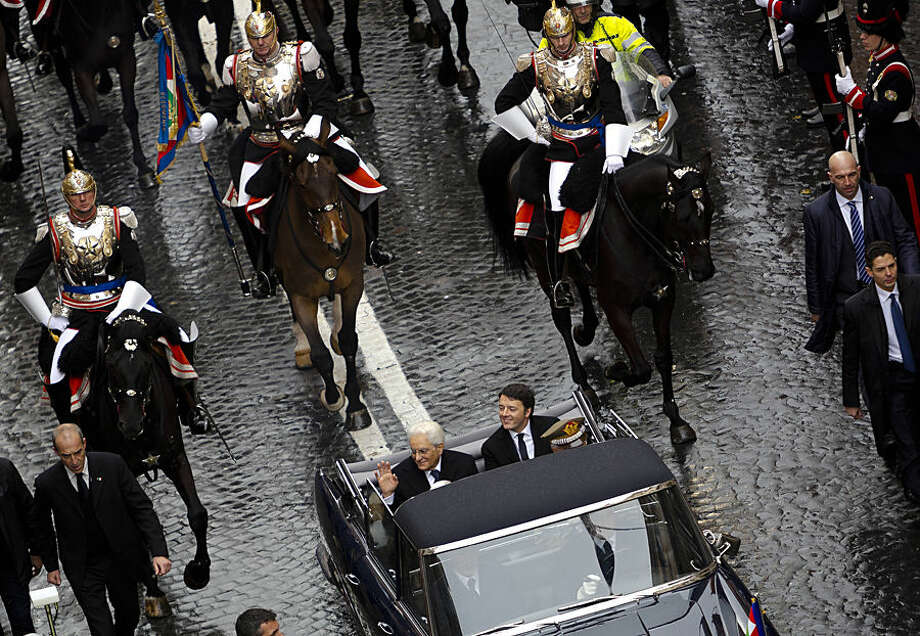 "Newly elected Italian President Sergio Mattarella, left, flanked by Italian Premier Matteo Renzi, waves from a car escorted by Cuirassier presidential horse guards heading to the Quirinal presidential palace to start his seven years as Italy's President in Rome, Tuesday, Feb. 3, 2015. Italy's new president, Sergio Mattarella, has taken the oath of office with a vow to fight corruption and organized crime and encourage the nation to embrace economic and electoral reform. The new head of state, whose brother, Piersanti Mattarella, was slain while governor of Sicily by the Mafia in 1980, denounced as ""alarming"" the spread of the Mafia from its traditional base in the south to northern cities. Mattarella, in his speech to Parliament Tuesday, also decried pervasive corruption, which he said robs citizens of resources meant for them and upsets market rules, ""penalizing the honest and the capable."" (AP Photo/Domenico Stinellis)"