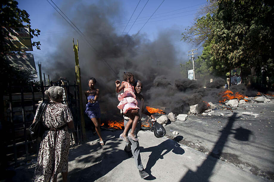 Residents run past a burning barricade set by public transportation drivers at the start a their two day strike over the cost of fuel in Port-au-Prince, Haiti, Monday, Feb. 2, 2015. Unions representing drivers say the government's cuts to the regulated cost of diesel and gasoline do not go far enough given the drop in global oil prices. (AP Photo/Dieu Nalio Chery)