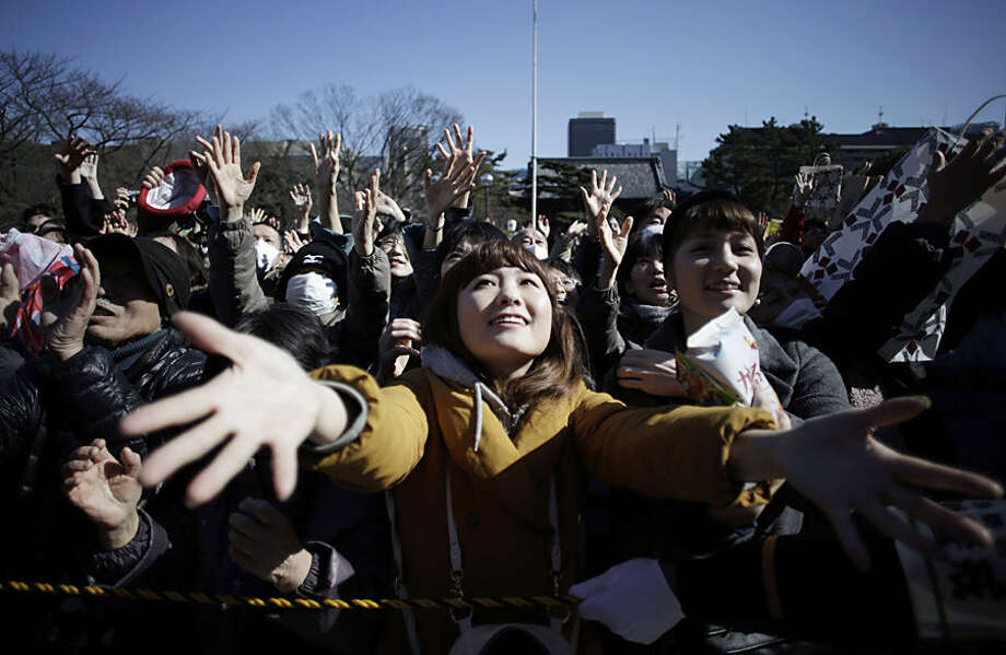 "People try to catch lucky beans scattered by celebrities during ""Mame-maki,"" a bean throwing ceremony, at Zojyoji Buddhist temple in Tokyo, Tuesday, Feb. 3, 2015. The ritual, performed annually to mark the beginning of the spring in the lunar calendar, is believed to bring good luck and drive away evil. (AP Photo/Eugene Hoshiko)"