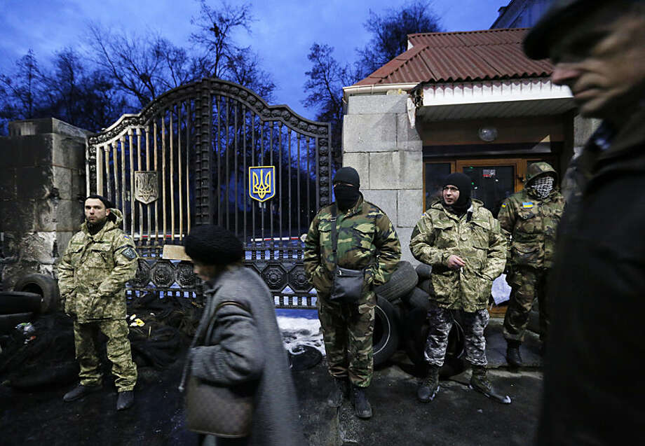 Volunteers of the Aidar battalion picket in front of the Ministry of Defense as they protest against a decision to change the leadership of the battalion in Kiev, Ukraine, Monday, Feb. 2, 2015. The Aidar battalion, a volunteer force, and the Defense Minister have agreed that the battalion will be divided into two units. Both of them - one headed by the old leader - will be incorporated into the Defense Ministry and will continue fighting in the country's east against pro-Russian separatists. (AP Photo/Sergei Chuzavkov)