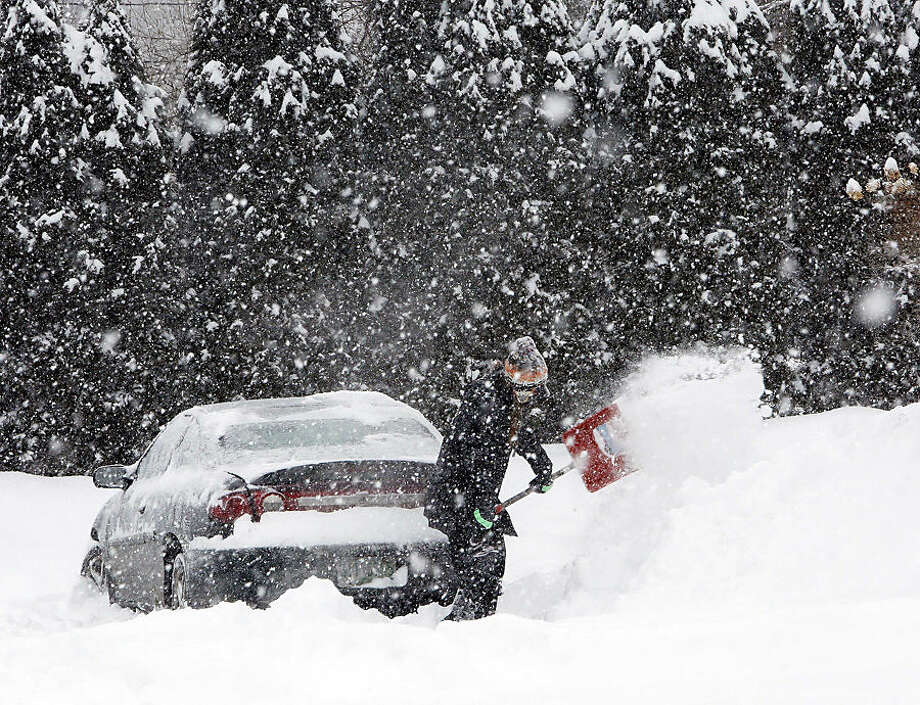 Krystal Koban removes snow from around her car during a winter storm, Monday, Feb. 2, 2015, in Henniker, N.H. (AP Photo/Jim Cole)