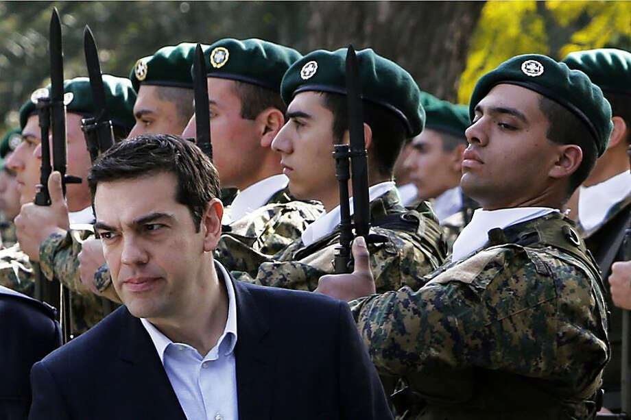Greek Prime Minister Alexis Tsipras reviews an honor guard at the Presidential Palace during a welcoming ceremony before a meeting with Cyprus' President Nicos Anastasiades in Nicosia Monday, Feb. 2, 2015. Tsipras is visiting Cyprus, his first trip abroad as prime minister since his election last month. It's customary for all newly-elected Greek prime ministers to conduct their first trip abroad to Cyprus because of the two countries' deep historic ties. (AP Photo/Petros Karadjias)