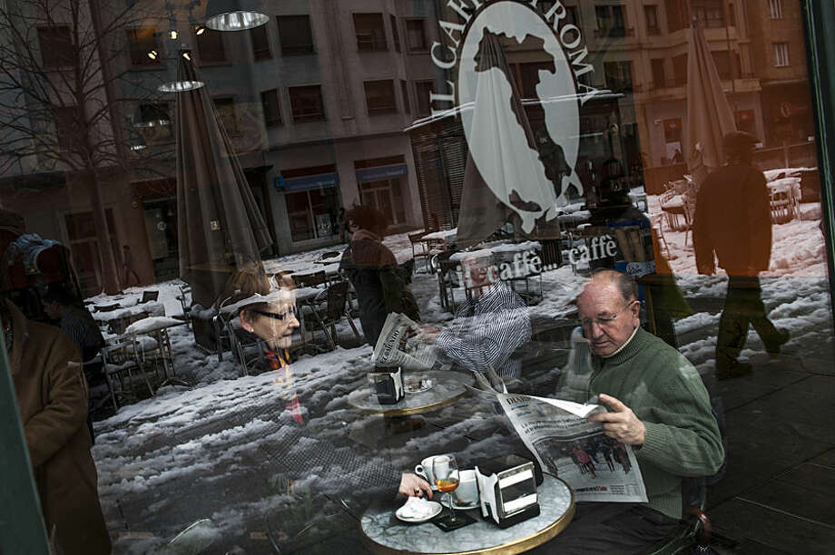 A man reads a newspaper as he enjoys a coffee as the snow reflects on the window of a coffee-bar, in Pamplona northern Spain, Monday, Feb. 2, 2015. (AP Photo/Alvaro Barrientos)