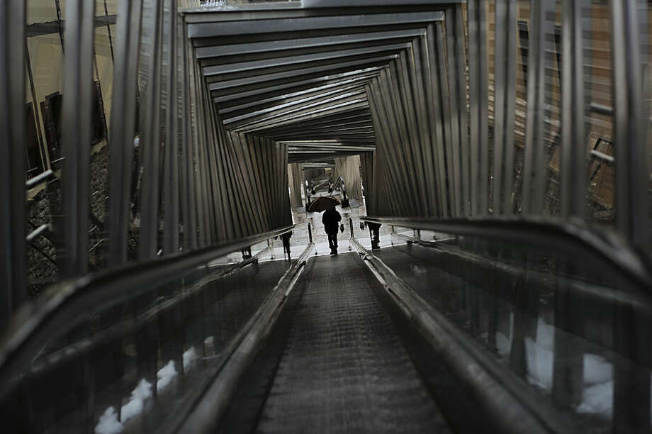 A woman shelters from the rain with an umbrella as she stands on an escalator to ascend up to the old city of Vitoria, northern Spain, Sunday, Feb. 1, 2015. (AP Photo/Alvaro Barrientos)