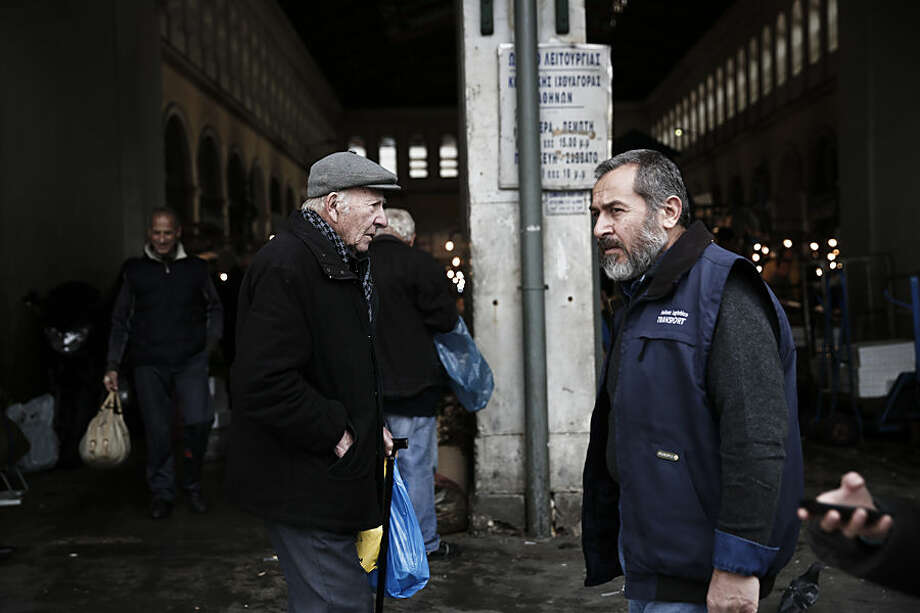 An elderly man carries a shopping bag as he walks past the central fish market in Athens, on Monday, Feb. 2, 2015. The fish market has long appealed to low-budget shoppers, and is a favorite destination in a country where incomes have dropped at least 30 percent, amid record-high unemployment, during the past five years of acute financial crisis. Greece's new finance minister, Yanis Varoufakis, is continuing his tour of European capitals with a visit to London, after receiving backing from France for efforts to ease the terms of a 240 billion-euro ($270 billion) bailout. (AP Photo/Petros Giannakouris )