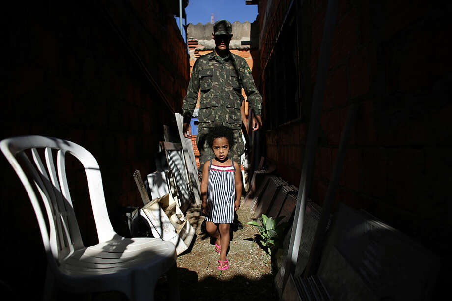 An army soldier visits a home during an operation to eradicate Aedes aegypti mosquito breeding sites, in the Brazlandia neighborhood of Brasilia, Brazil, Wednesday, Feb. 17, 2016. The Aedes aegypti mosquito is a vector for the spread of the Zika virus and it lives largely inside homes and can lay eggs in even a bottle-cap's worth of stagnant water. (AP Photo/Eraldo Peres)