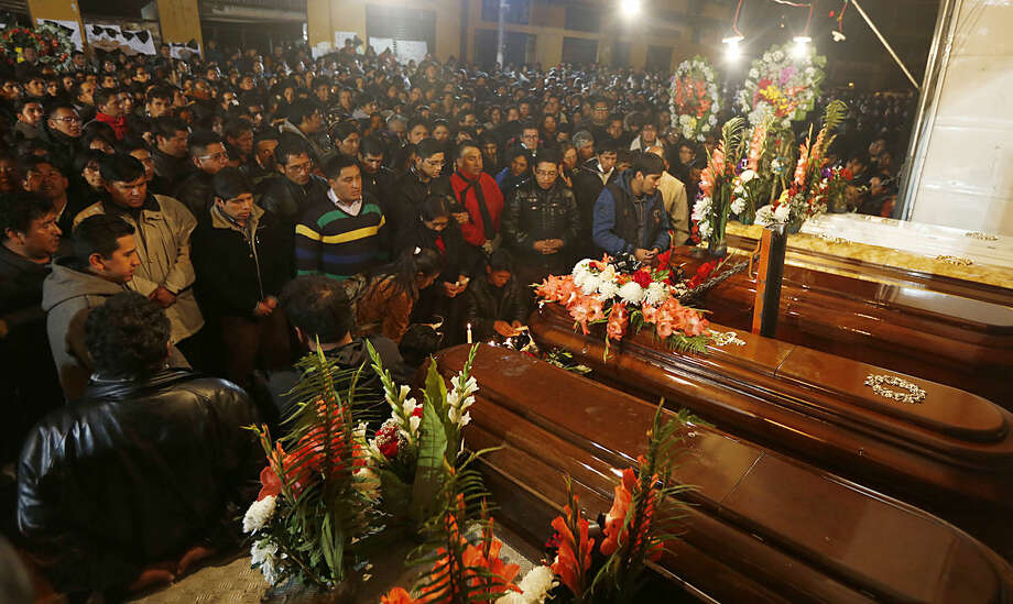 Family and friends pray before the coffins containing the remains of the workers who died of asphyxiation, in front of the municipal building that was set on fire by protesters, and where the workers died, in El Alto, Bolivia, Wednesday, Feb. 17, 2016. Several workers died Wednesday and dozens were injured in the opposition-run highlands city of El Alto. The fire was ignited by protesters following a march by residents demanding better schools and more teachers. (AP Photo/Juan Karita)