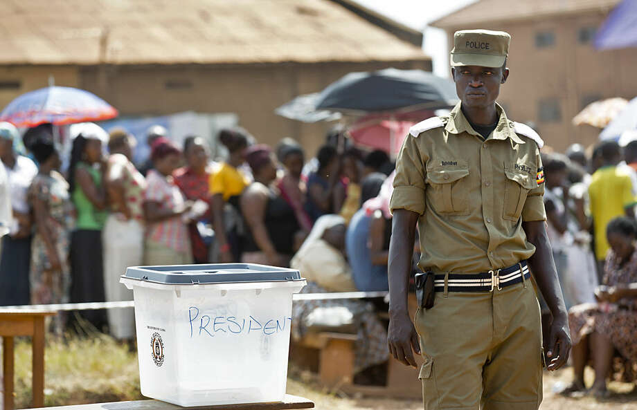 A policeman stands guard by an empty ballot box at a polling station where five hours after voting was due to start no voting papers had yet arrived, in the capital Kampala, Uganda Thursday, Feb. 18, 2016. Ugandans voted Thursday in presidential elections seen as the toughest challenge yet for the country's long-time president, but voting was marred by delays of voting materials in many places, and people complained of an apparent shutdown of social media sites like Twitter and Facebook. (AP Photo/Ben Curtis)