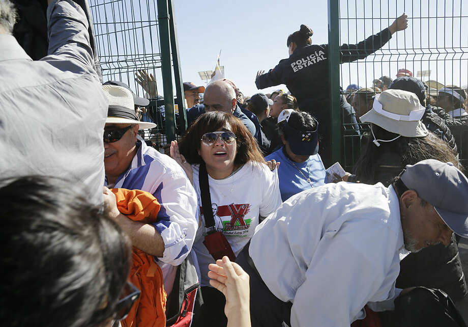 People push forward as they enter the area where Pope Francis will celebrate an outdoor Mass, in Ciudad Juarez, Mexico, Wednesday, Feb. 17, 2016. Just before the start of his Mass in a large field in Juarez, Francis is expected to make a short walk to the border fence along the Rio Grande. (AP Photo/Gregory Bull)