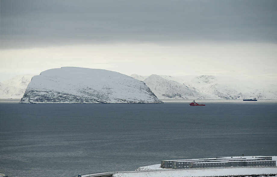 In this photo taken Thursday, Feb. 4, 2016, showing a view towards the refugee camp in Hammerfest, northern Norway, and an inlet from the Barents Sea. After hiding below the horizon for two long months, the sun has finally risen in Hammerfest, casting a pale pink hue over the Arctic landscape surrounding the world's northernmost refugee shelter. (AP Photo/Alastair Grant)