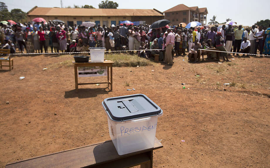 A ballot box sits empty while voters queue at a polling station where five hours after voting was due to start no voting papers had yet arrived, in the capital Kampala, Uganda, Thursday, Feb. 18, 2016. Ugandans voted Thursday in presidential elections seen as the toughest challenge yet for the country's long-time president, but voting was marred by delays of voting materials in many places, and people complained of an apparent shutdown of social media sites like Twitter and Facebook. (AP Photo/Ben Curtis)