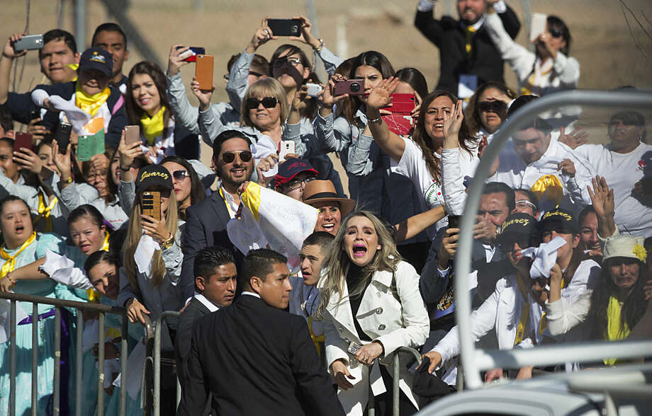 People wave and take pictures of Pope Francis as he leaves Abraham Gonzalez International Airport upon arrival to Ciudad Juarez, Mexico, Wednesday, Feb. 17, 2016. The pontiff is scheduled to wrap up his trip to Mexico on Wednesday with a visit in a Ciudad Juarez prison, just days after a riot in another lockup killed 49 inmates, and a stop at the Texas border when immigration is a hot issue for the U.S. presidential campaign. (AP Photo/Ivan Pierre Aguirre)