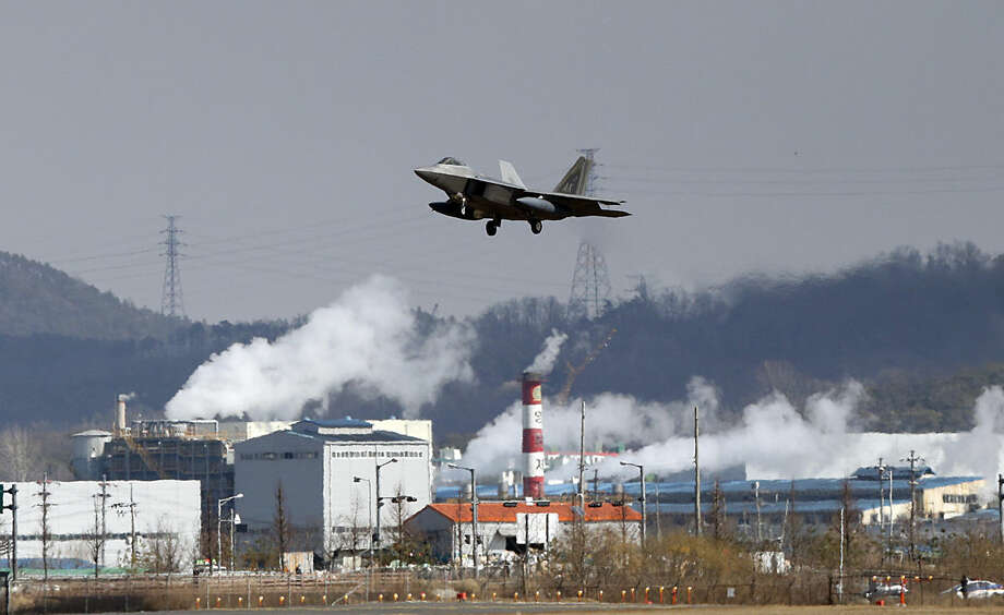 One of four U.S. F-22 stealth fighters flies over Osan Air Base in Pyeongtaek, South Korea, Wednesday, Feb. 17, 2016. Four U.S. F-22 stealth fighters flew over South Korea on Wednesday in a clear show of power against North Korea, a day after South Korea's president warned of the North's collapse amid a festering standoff over its nuclear and missile ambitions. (AP Photo/Lee Jin-man)