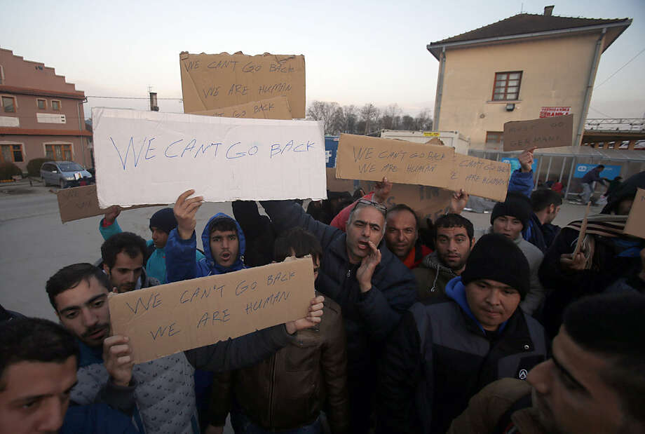 Migrants shout slogans and protest at the train station in Sid, about 100 km west from Belgrade, Serbia, Wednesday, Feb. 17, 2016. More than 200 people have been camping at a border train station after they were sent back to Serbia from Croatia amid tightened rules for migrants seeking entry into the European Union. (AP Photo/Darko Vojinovic)