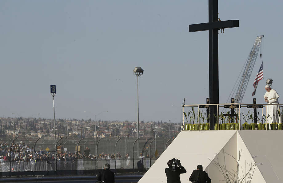 Hundreds of people gathered a few yards away on the U.S. side watch as Pope Francis prays near the U.S.-Mexico border fence along the Rio Grande, in Ciudad Juarez, Mexico, Wednesday, Feb. 17, 2016. After a brief moment of prayer, Francis walked down the ramp and got back on his popemobile to head for the fairgrounds, where he celebrated his last Mass during a five-day Mexico tour. (AP Photo/Gregorio Borgia)